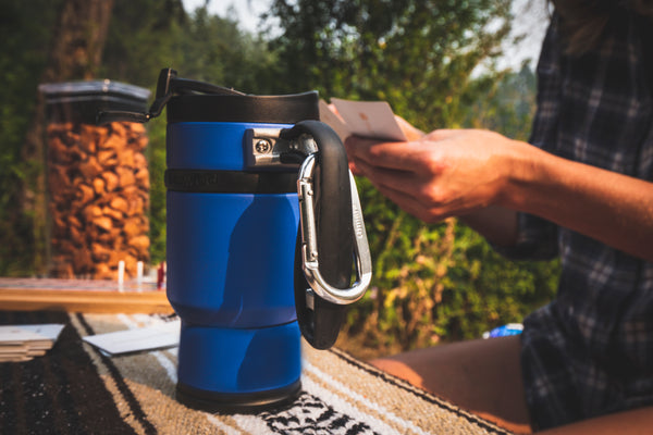 double shot coffee maker on park bench in the forest mountain with people playing cards