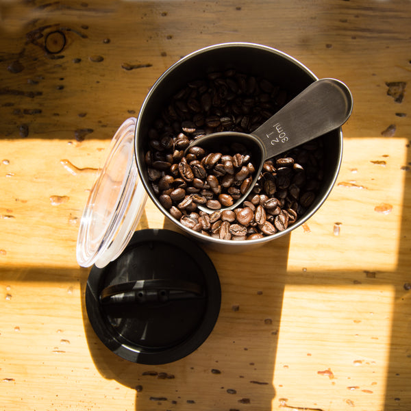 coffee scoop in coffee beans on wooden table