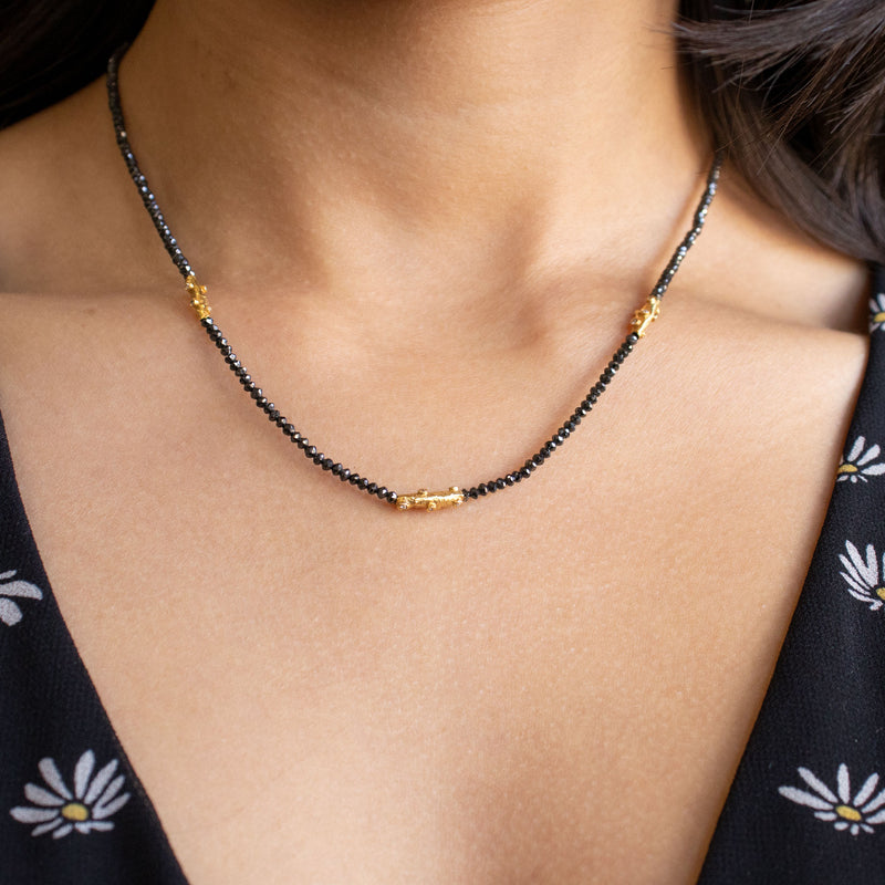 Necklace featuring black diamond beads and three yellow gold and white diamond branch accents, with an oval clasp with gold granulation details. Length of 18 inches.  On a neck.