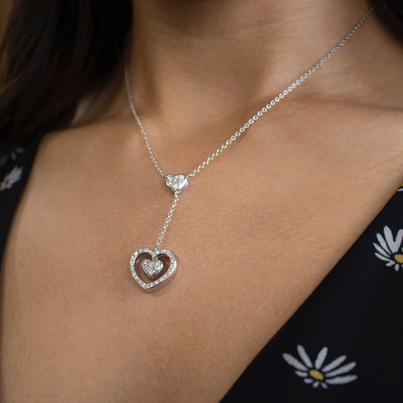 18 karat white gold lariat necklace featuring a double heart drop set with pavé diamonds, suspended from a central pavé set diamond heart 0.63ctw in a length of 15.5 inches. On a neck.