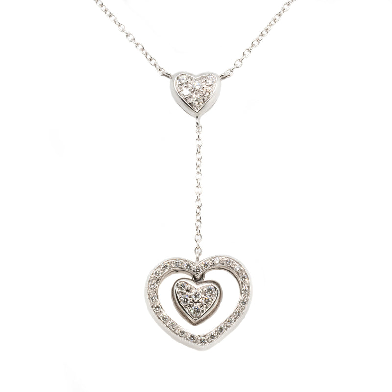 18 karat white gold lariat necklace featuring a double heart drop set with pavé diamonds, suspended from a central pavé set diamond heart 0.63ctw in a length of 15.5 inches.