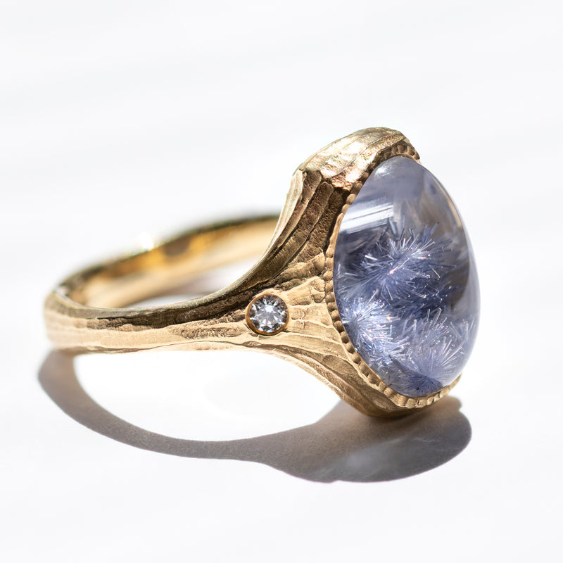 18 karat yellow gold ring designed by Michael Endlich featuring a textured bezel set oval cabochon Dumortierite 9.05ct flanked by two flush-set diamonds 0.10ctw, with an allover matte redwood bark texture, in a finger size 8.