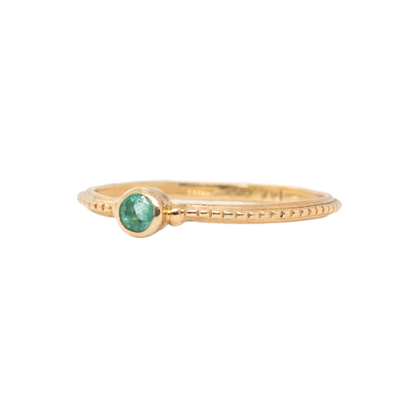 14 karat yellow gold ring in a beaded pattern featuring a 3mm round bezel set emerald. Finger size 6.5.