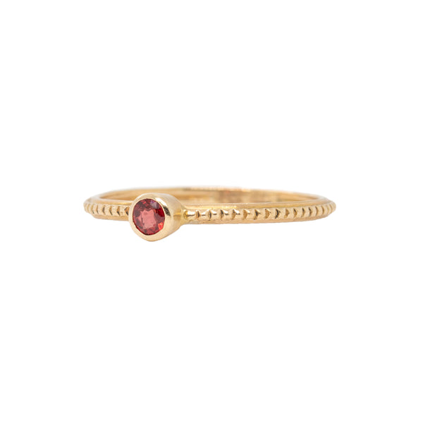 14 karat yellow gold ring in a beaded pattern featuring a 3mm round bezel set pink sapphire. Finger size 6.5.