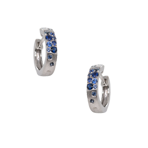 14 karat white gold hinged hoops featuring blue sapphires (0.32ctw) flush set down the front half of the earrings in a confetti style, completed with a satin finish.