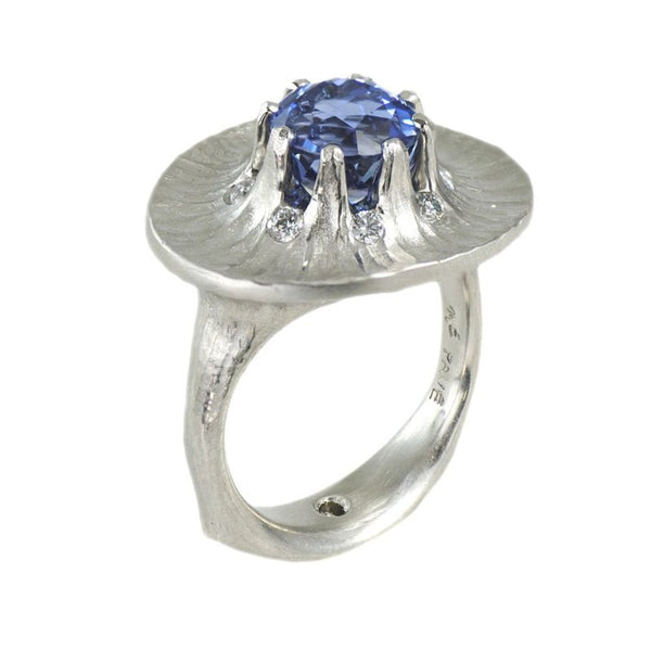 Platinum ring featuring an 8-prong set round Blue Sapphire 4.30ct in the center of a wide horizontal scalloped design accented by 8 round brilliant diamonds 0.23ctw surrounding the sapphire center set amongst the prongs finished with a redwood bark texture in a finger size 7.5.
