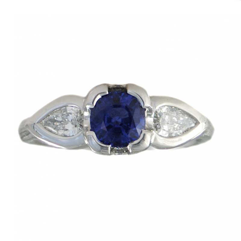 Platinum ring designed featuring a Ceylon Blue cushion cut Sapphire 1.00ct set in a four prong center and flanked on either side by  bezel set pear shaped Diamonds 0.33ctw, accented by a round brilliant Diamond on each side the the ring's profile and finished with a redwood bark texture in a finger size 6.5.