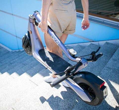 Man on stairs transports folding electric scooter