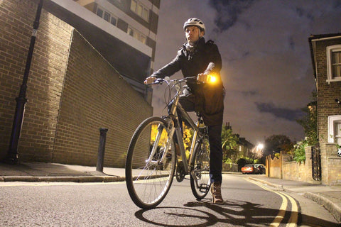 Man on a bicycle in the dark with WingLights turn signals and position lights on