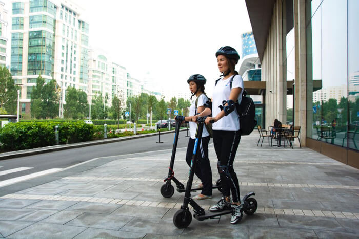 Two women with helmet on electric scooters