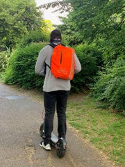 Man on electric scooter with High Visibility Backpack Cover | CYCL