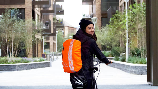 Woman on bicycle with high visibility backpack cover | CYCL