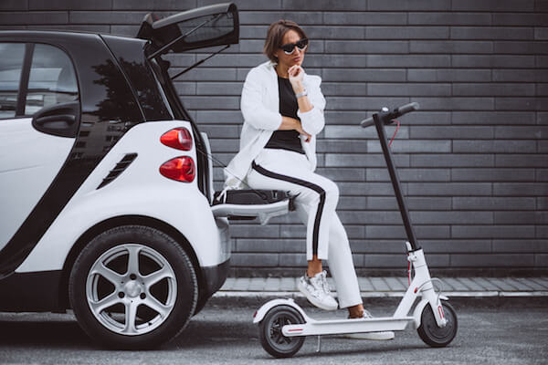 young woman sitting car with electric scooter