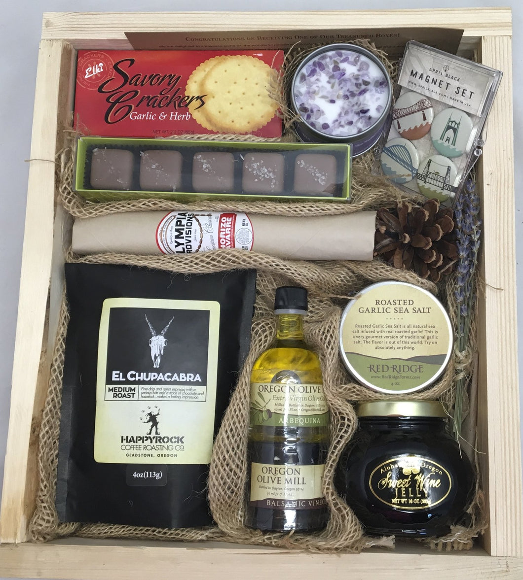Sample box containing coffee, olive oil, balsamic vinegar, jam, garlic salt, salami, candle, magnet set, chocolate truffles, and crackers.