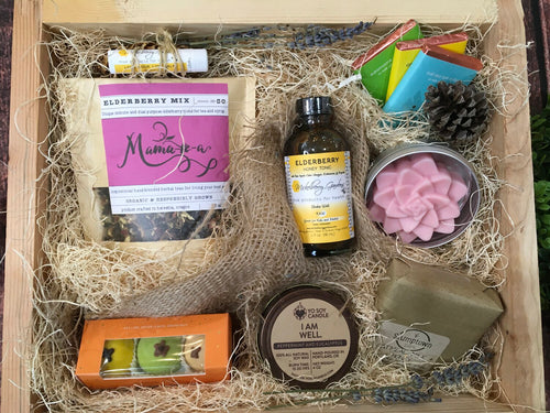 Sample box containing loose leaf tea, chocolate truffles, soy candle, elderberry tonic, body butter, soap, lip balm, and chocolate bars.