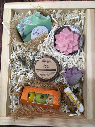 Sample box containing body butter, soap, soy candle, chocolate truffles, and lip balm.