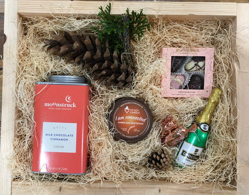 Sample box containing a soy candle, drinking chocolate, chocolate hearts, and chocolate champagne.