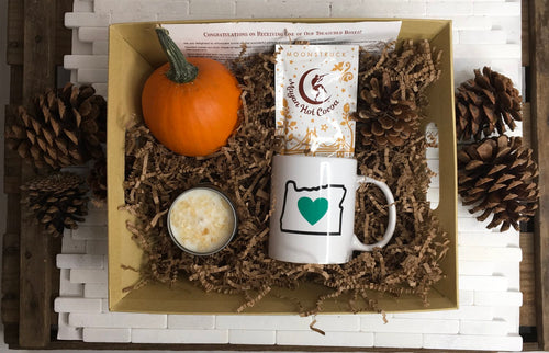 Sample box containing an Oregon Luv mug, a candle, a pumpkin, and hot chocolate.