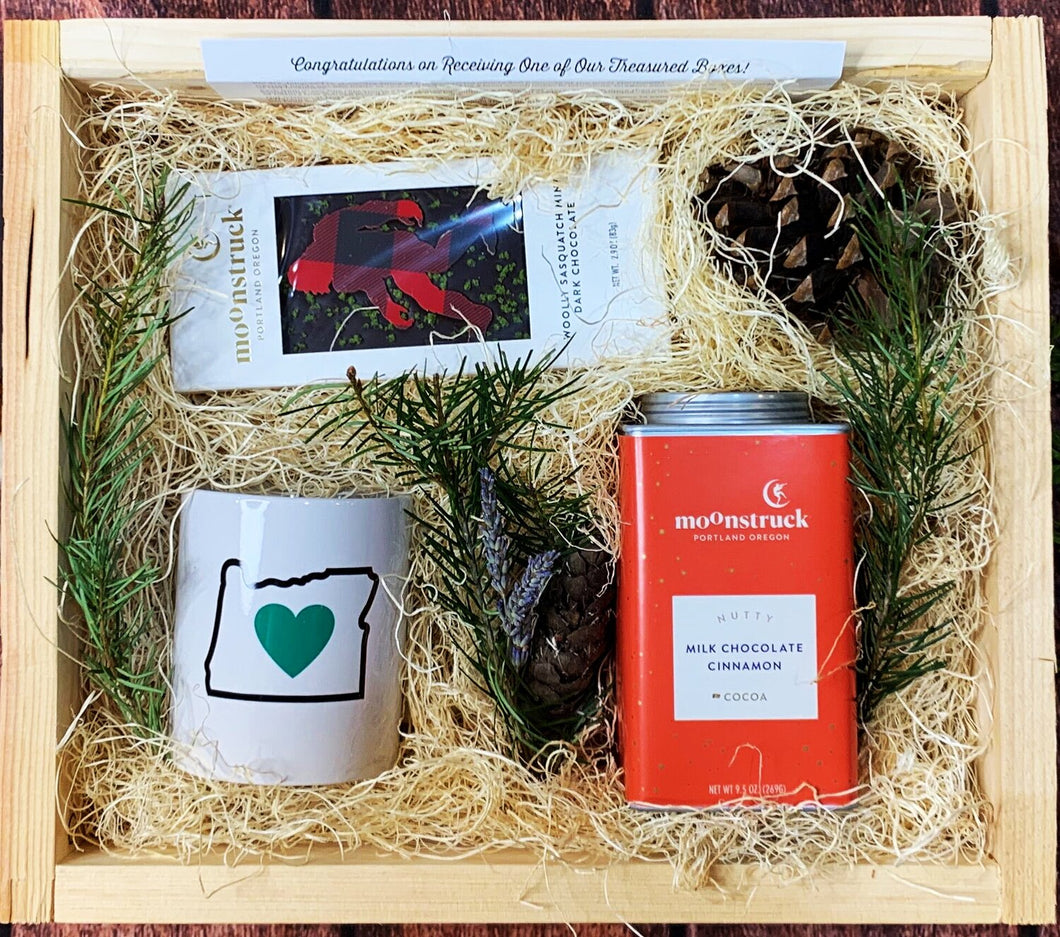 Sample box containing Oregon Luv mug, sasquatch chocolate bar, hot chocolate.