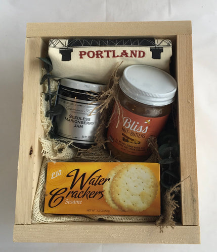 Sample box containing crackers, nut butter, jam, and a tea towel.