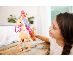 Girl playing with Barbie and horse