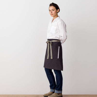 Bistro Apron on Model, Side View, Charcoal Black with Tan Straps, Half Apron, Reluctant Trading