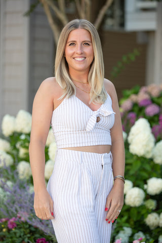 Alexa Modero headshot photo for Hudson Main interview. wearing white and standing in front of pink and white flowers.
