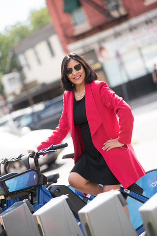 Lorena Standing with City Bikes in McGinley Square Jersey City New Jersey. Wearing a red blazer and black dress while smiling in sunglasses