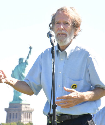Sam Pesin President of Friends of Liberty State Park giving a speech in front of the Statue of Liberty at the rally to save the park. Standing in front of a microphone wearing a blue button down speaking with his arms about the park.