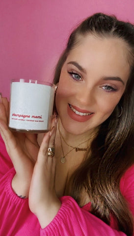 Samantha from Hot Stuff Candles posing with her popular candle scent with a pink wall background for Hudson Main Article
