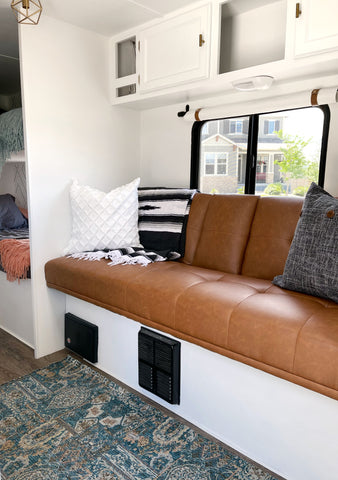 Camper renovation living room makeover with new faux leather futon converted to trailer couch