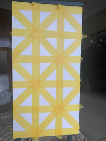 Taping geometric patterns to dresser with yellow Frog Tape, painting with Wise Owl One Hour Enamel and a roller