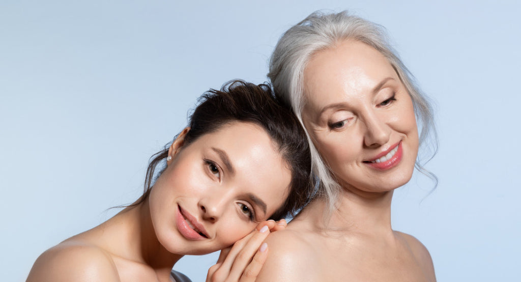 younger brunette woman rests head on shoulder of older grey haired woman