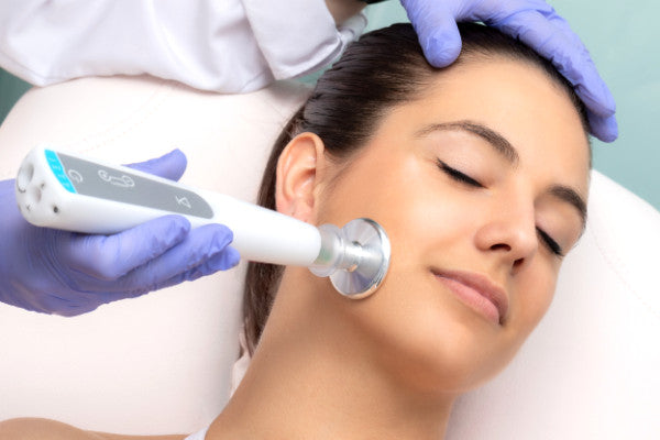 woman with head on pillow receiving plasma pen treatment on face