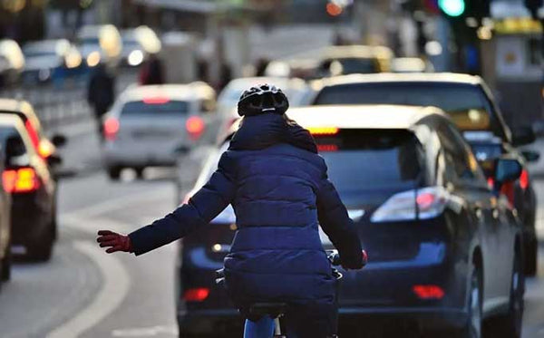 Woman riding a bike on the street making a left hand turn signal