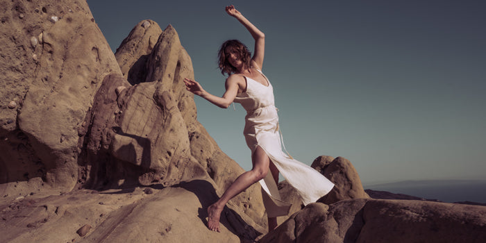 Sakti Rising sustainable ethical yoga apparel; woman dancing on cliff