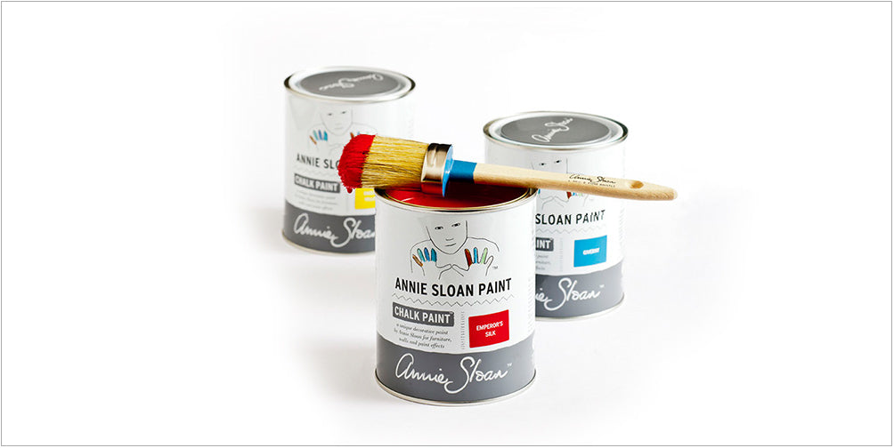 Three tins of chalk paint with a paint brush on top
