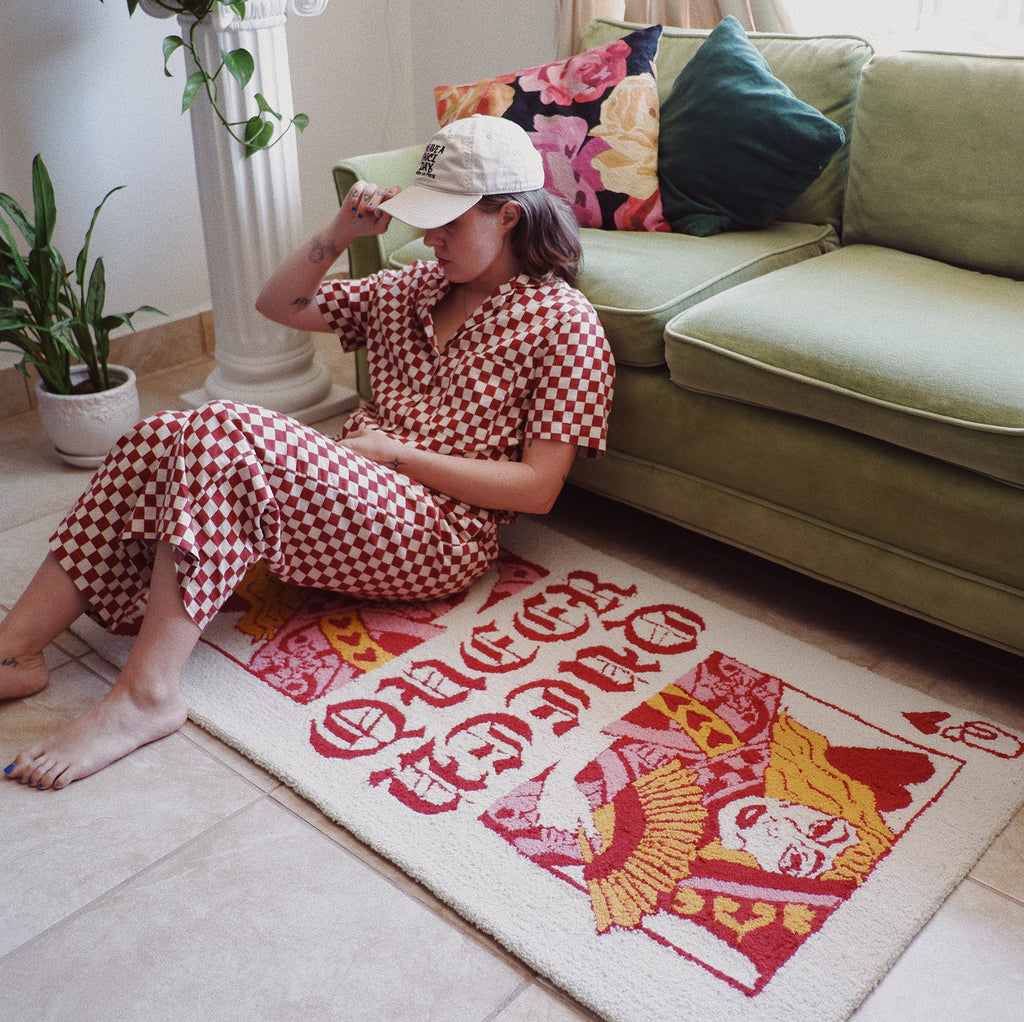 AJ sitting on the Queer of Hearts rug