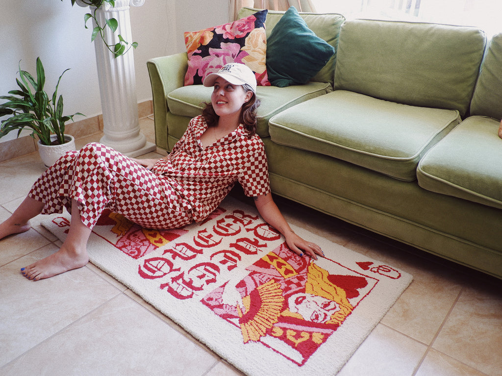 AJ sittin on a Queer of Hearts rug (a rug that looks like a Queen of Hearts playing card, but with a drag queen) next to a green couch surrounded by plants.