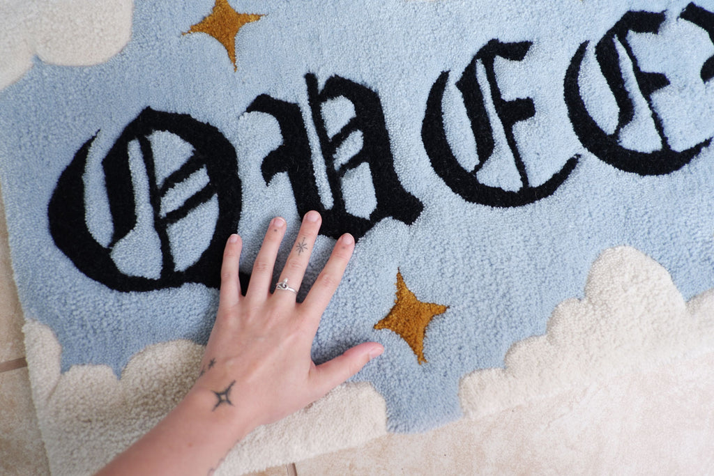 AJ's hand resting on the Queer Magic rug