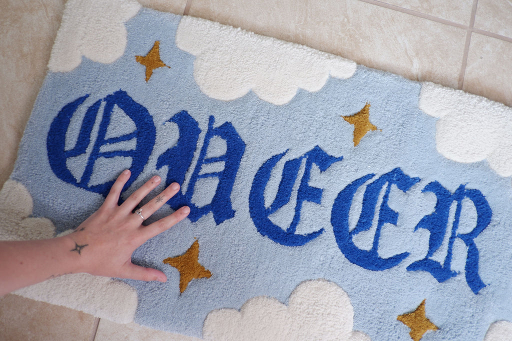 """Queer Magic Rug: a hand-tufted rug with the word """"QUEER"""" in a blackletter style type with stars and clouds surrounding it."""