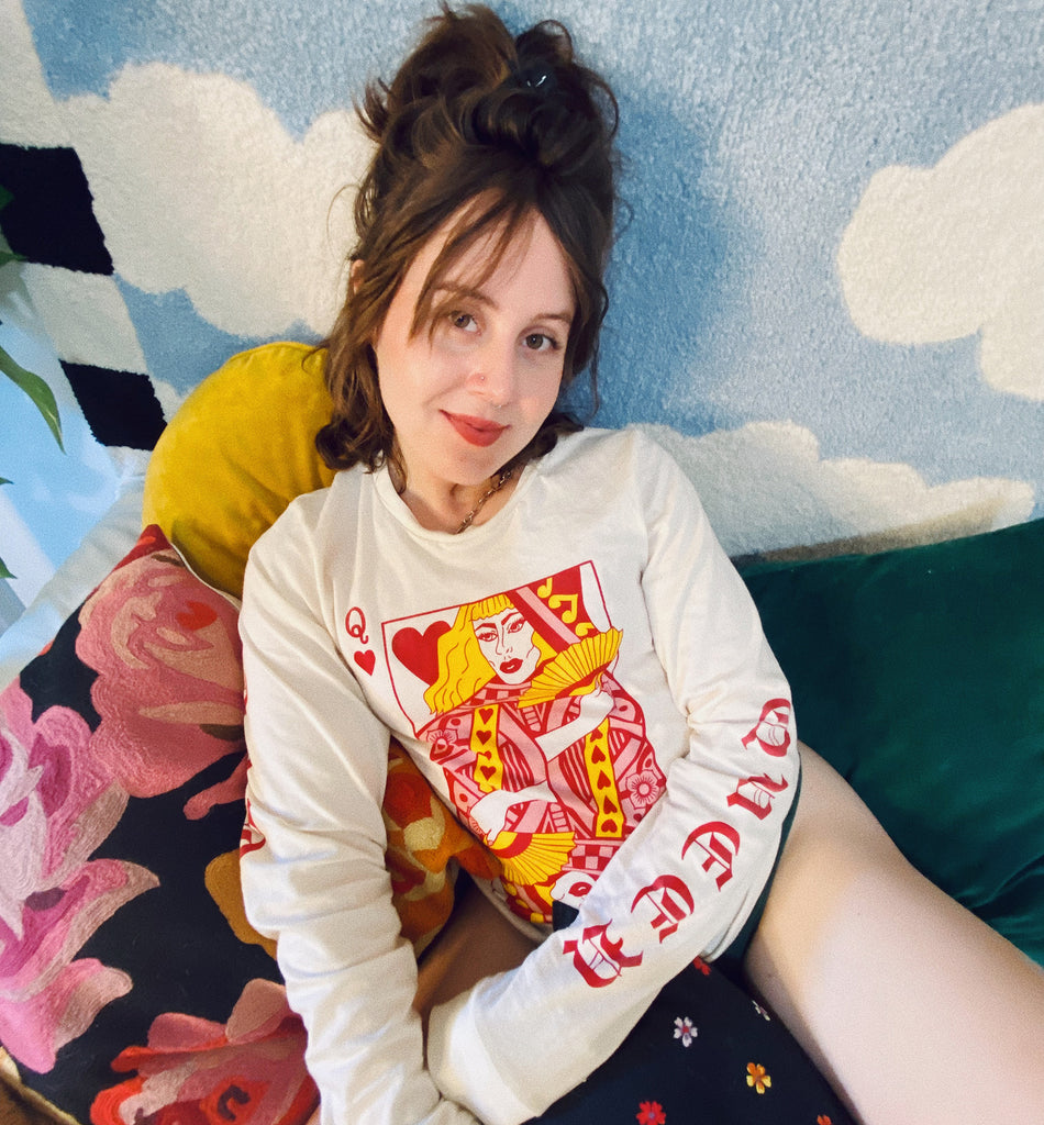 AJ sitting on a bed in front of a rug with sky and clouds wearing the Queer of Hearts long sleeve shirt.
