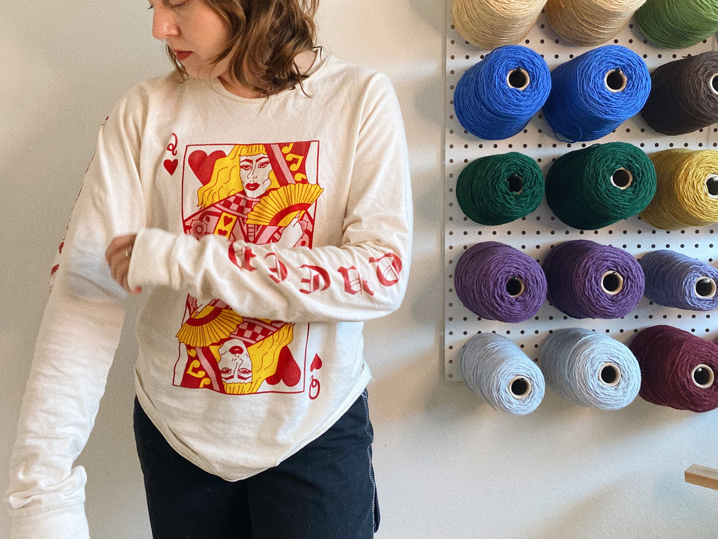AJ wearing the Queer of Hearts shirt, standing next to a pegboard full of colorful yarn cones.