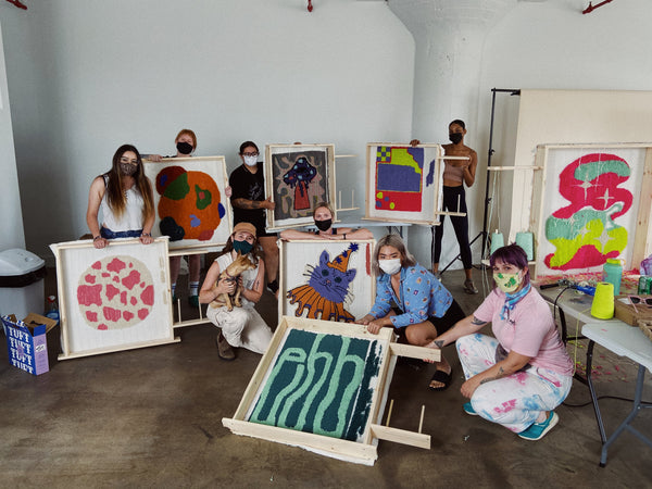 Workshop participants with their finished tufted pieces