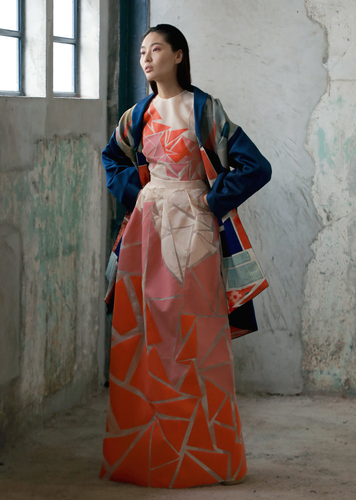 woman wearing blue patchwork boro coat and floor-length geometric skirt with matching orange pink white geometric top