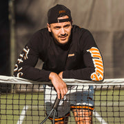 Man on tennis court wearing black long sleeve