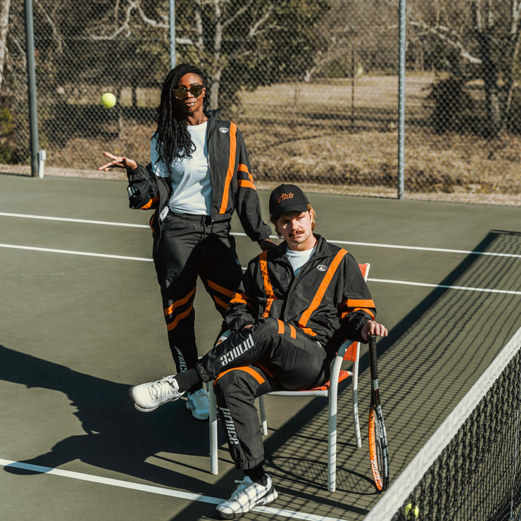 Man and woman on a tennis court wearing black track jacket and black windbreaker pants