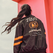 Woman wearing black track jacket with Tito's Handmade Vodka logo