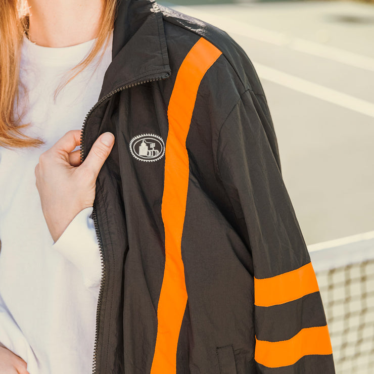 Woman wearing black track jacket with pot still design on left chest