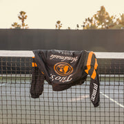 Black track jacket laying on top of tennis net